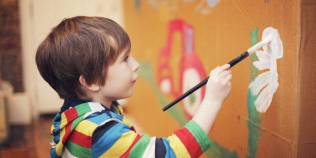 A young boy doing a large painting on a piece of card at