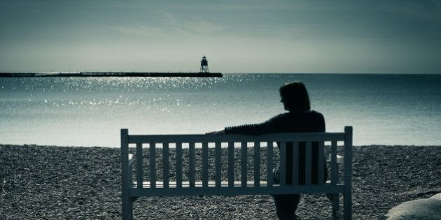 Woman in silhouette, sitting on a bench in a moody landscape at water's edge. The lone woman may be widowed, divorced, or lonely, sitting in solitude, contemplating her grief, sadness, or depression. The lighthouse in the distance is a symbol of finding hope or direction in a sea of troubles.