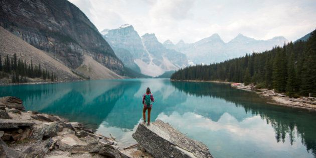 A woman standing on a scenic lookout overlooking Moraine Lake in Alberta,