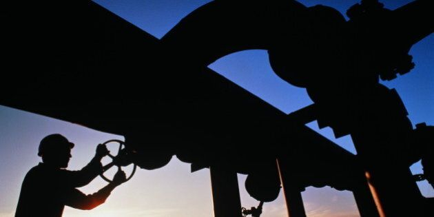 Worker turning valve on geothermal pipeline, silhouetted against dusk