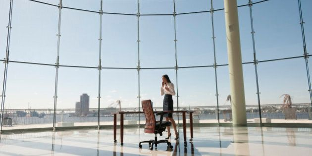 Businesswoman working in large office with glass