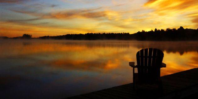 Adirondack chair on cottage deck at sunrise Sharbot Lake, Ontario,