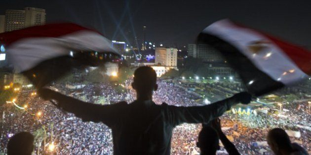 A Egyptian man waves national flags as an army helicopter flies over supporters of Egyptian Armed Forces...