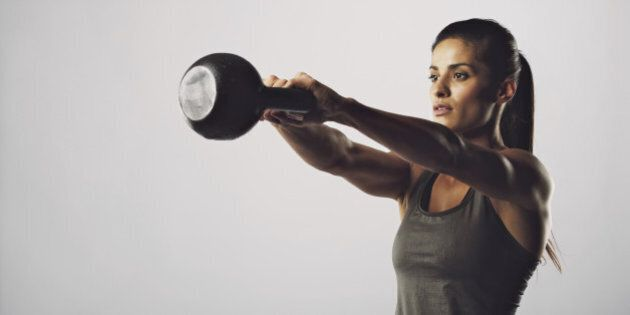 Young fitness female exercise with kettle bell. Mixed race woman doing gym workout on grey