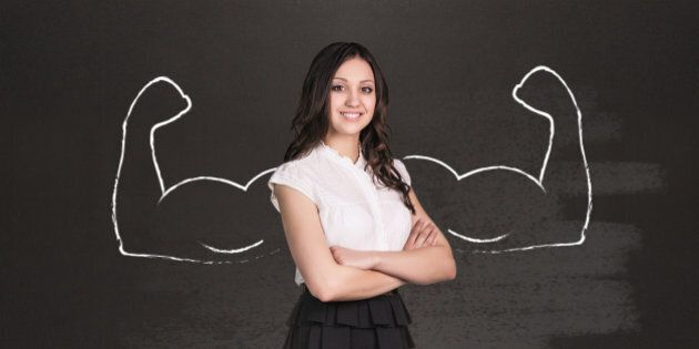 Business woman with drawn powerful hands. Black chalkboard