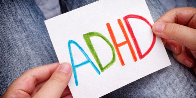 Young boy holds ADHD text written on sheet of paper. ADHD is Attention deficit hyperactivity disorder. Close up.