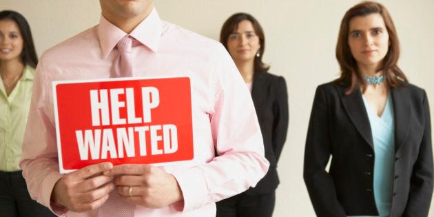 Portrait of three businesswomen standing with a businessman holding a help wanted signboard