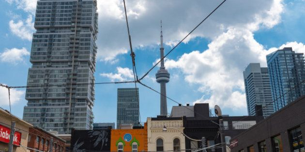 TORONTO, ONTARIO, CANADA - 2016/08/18: CN Tower seen from double decker bus with tourists enjoying a...