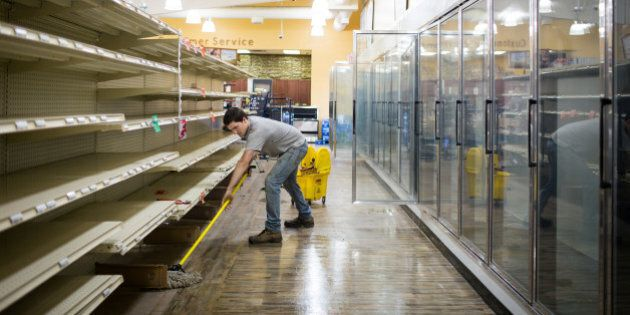 A crew member mops the inside of a grocery store after clearing all the expired food off the shelves...