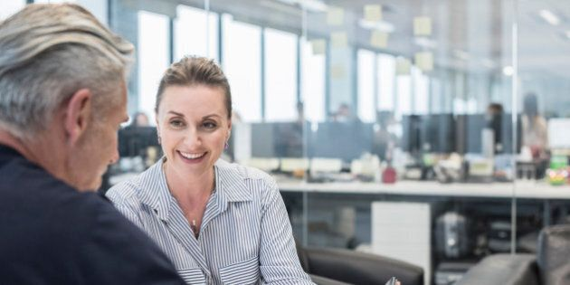 Two business people in informal meeting with digital tablet. Woman smiling towards man, explaining. Male client with female business woman in modern open plan office