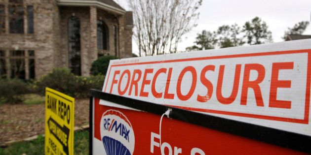 A bank repo and foreclosure for sale signs sit outside a foreclosed home Saturday, Jan. 10, 2009 in Houston....