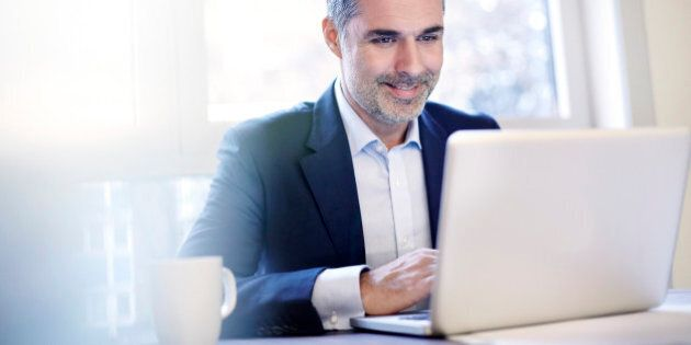 Businessman working on a laptop smiling.