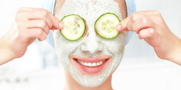Funny young girl with a mask for skin face and cucumbers on