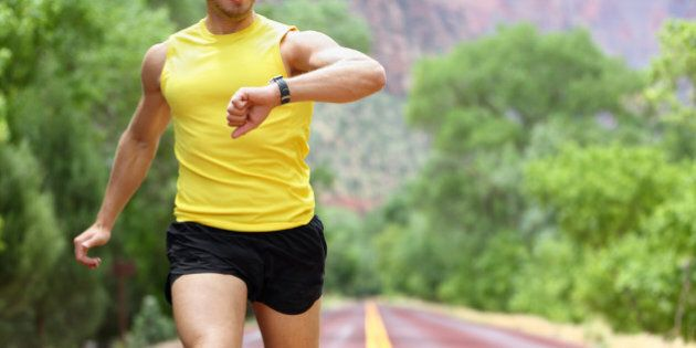 Runner with heart rate monitor sports watch. Man running looking at his pulse outside in nature on