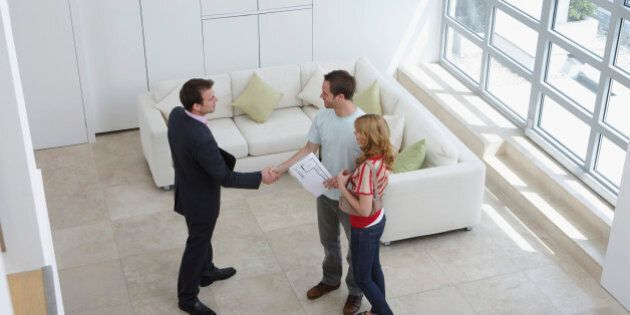 Real Estate Agent With Couple Buying New
