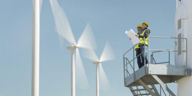 Workers standing on wind turbine in rural landscape