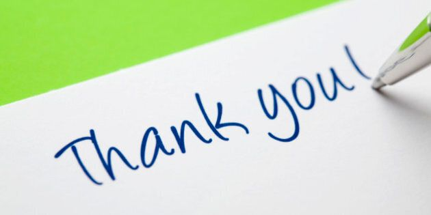 'In the process of writing a thank you card. Green backdrop imparting a light feel to the image -- eg,...