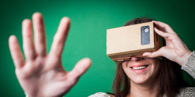 Color shot of a young woman looking through a cardboard, a device with which one can experience virtual...