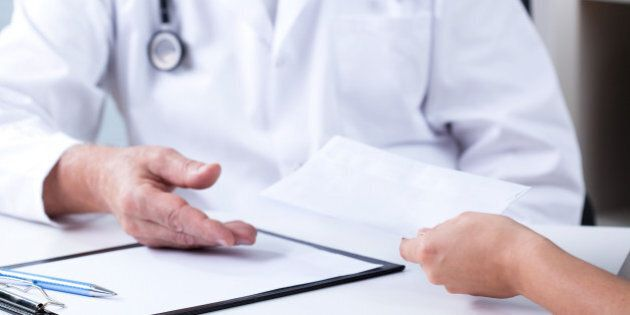 Senior male doctor and payment for private consultation