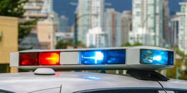 Police car lightbar emergency lights flashing, with city buildings in the