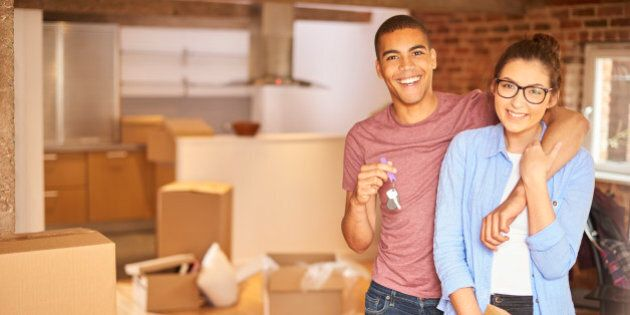 a young couple unpack their belongings as they settle into their new loft apartment . They are hugging and looking to camera smiling holding their keys aloft .