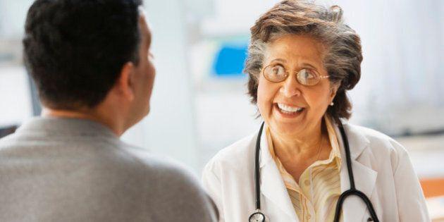 Senior Hispanic female doctor talking to