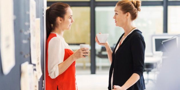 Side view of businesswomen discussing while having coffee in