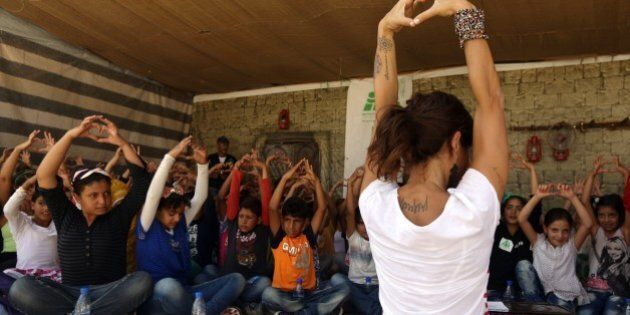 Lebanese Yogi Danielle Abi Saab and Syrian schoolchildren flash the love sign during an introductory...