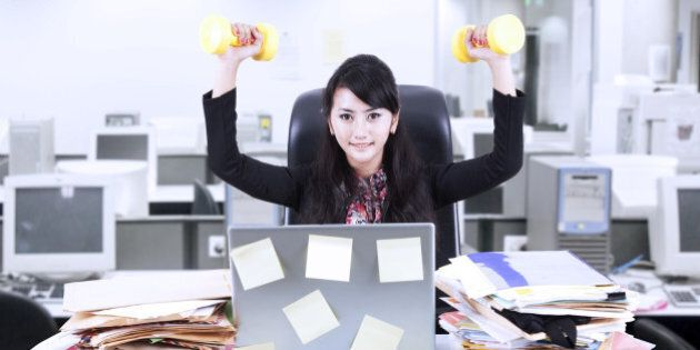 Young businesswoman doing exercise in front of her laptop with lots of sticky