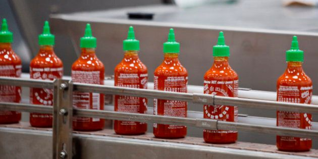 Bottles of the Sriracha hot sauce travel down a conveyor belt to be boxed for shipment at the Huy Fong Foods Inc. facility in Irwindale, California, U.S., on Monday, Nov. 11, 2013. A judge denied the city of Irwindale's request for a temporary restraining order and set a hearing for November 22 to determine whether the hot-sauce factory should be shut down while it fixes alleged odor problems. Photographer: Patrick T. Fallon/Bloomberg via Getty Images