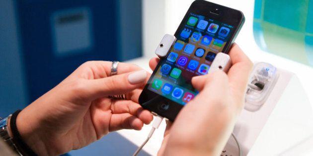 A customer inspects an Apple Inc. iPhone 5 smartphone inside a Portugal Telecom SGPS SA mobile communications...