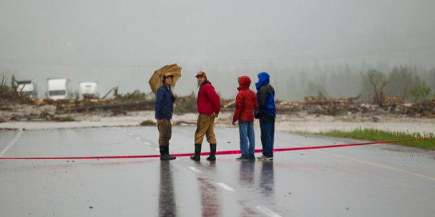 CANMORE, CANADA - JUNE 20: Bystanders look over debris deposited by Cougar Creek as it flowed up and...