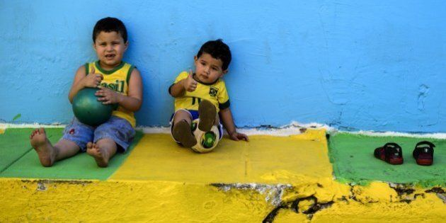Young Brazilian children pose on a street decorated in the colours of the Brazilian national flag in...