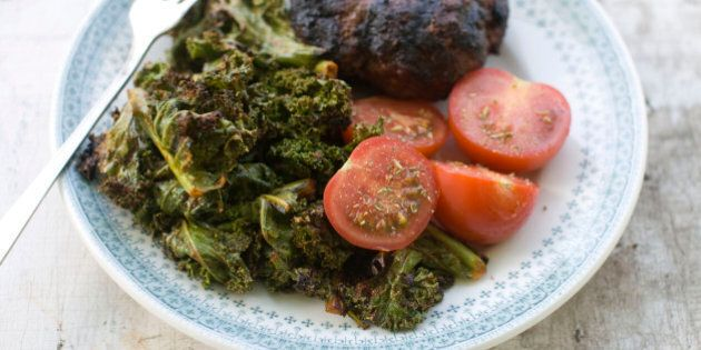 In this image taken on July 9, 2012, garlicky grilled kale served with a burger and fresh tomatoes makes...
