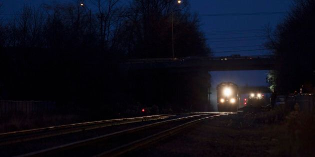 [UNVERIFIED CONTENT] Westbound CN freight train led by a SD70I locomotive passes a work gang installing...
