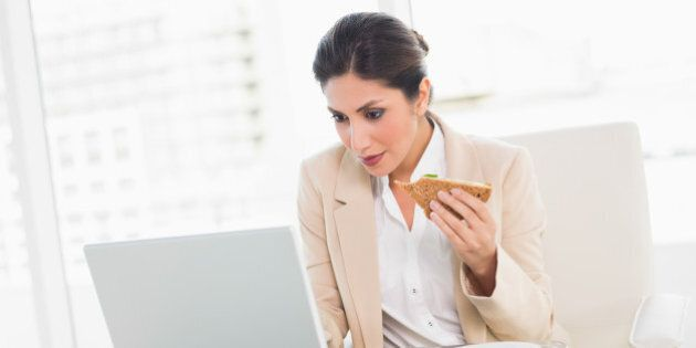 Focused businesswoman eating lunch as she is working at the