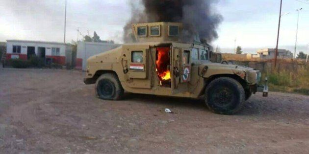 A picture taken with a mobile phone shows an armoured vehicle belonging to Iraqi security forces in flames...