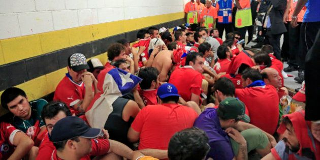 Chilean fans are surrounded by security personnel after breaking into Maracana Stadium before the group...