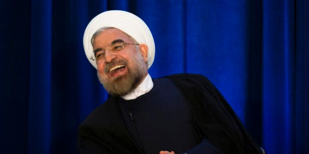 Iranian President Hassan Rouhani laughs during a address and discussion hosted by the Asia Society and...