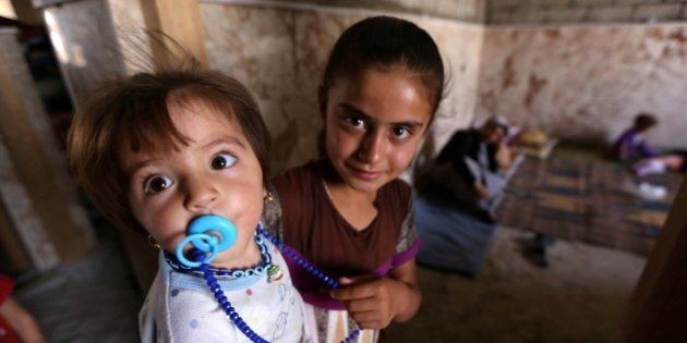 Iraqi Yazidi children who fled the violence in the northern Iraqi town of Sinjar with their family, stand...