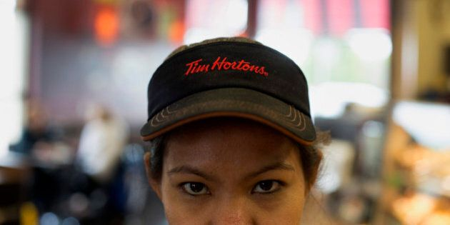 An employee wears a Tim Hortons Inc. visor at a restaurant in Oakville, Ontario, Canada, on Monday, Sept....