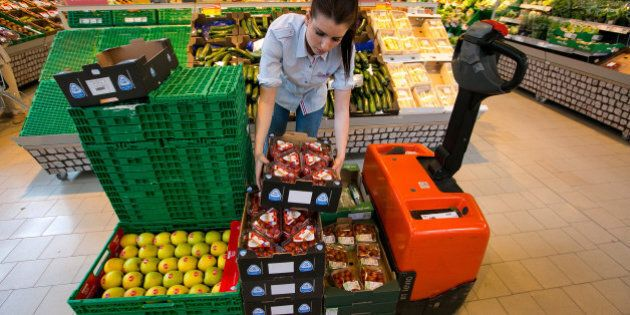 An employee unloads punnets of strawberries from a pallet inside a Rewe supermarket, operated by the...