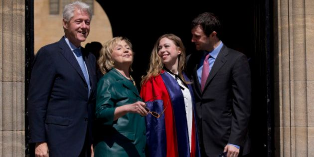 Former U.S. Secretary of State Hillary Rodham Clinton, second left, takes off her sunglasses to pose for a group photograph with her husband former U.S. President Bill Clinton, left, their daughter Chelsea, second right, and her husband Marc Mezvinsky, as they leave after they all attended Chelsea's Oxford University graduation ceremony at the Sheldonian Theatre in Oxford, England, Saturday, May 10, 2014.  Chelsea Clinton received her doctorate degree in international relations on Saturday from the prestigious British university. Her father was a Rhodes scholar at Oxford from 1968 to 1970.  The graduation ceremony comes as her mother is considering a potential 2016 presidential campaign.  (AP Photo/Matt Dunham)
