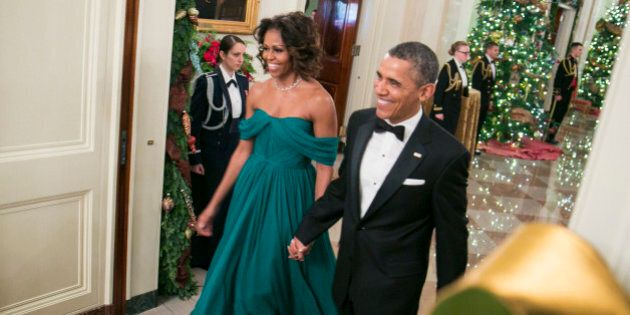 WASHINGTON, DC - DECEMBER 08: President Barack Obama (R) and First Lady Michelle Obama arrive for a reception...