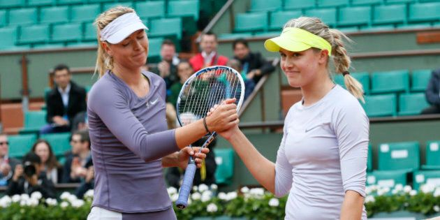 Russia's Maria Sharapova (L) shake hand with Canada's Eugenie Bouchard after winning their French tennis...