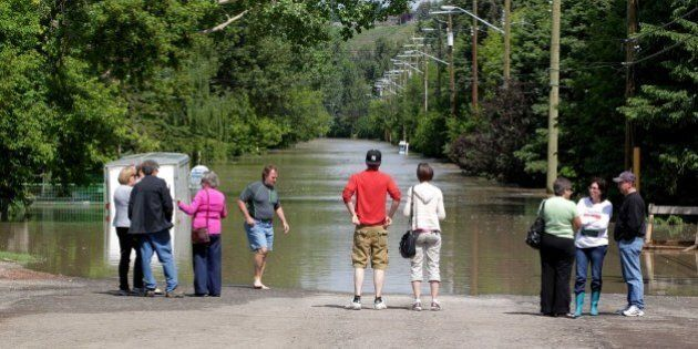 People gather in the Bowness neighbourhood looking down a water-filled street near the flooded Bow River...