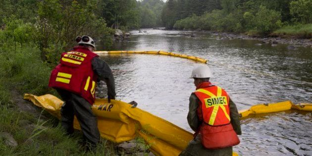 Environment workers lay booms on the Chaudiere River near Lac-Megantic, Que., to contain the crude oil...