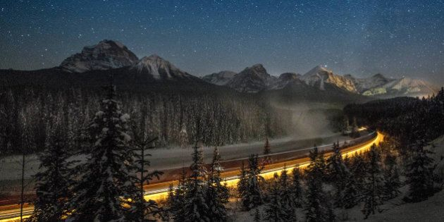 Cargo train passes through the famous 'Morant's Curve' offering a beautiful view of the frozen Bow River...
