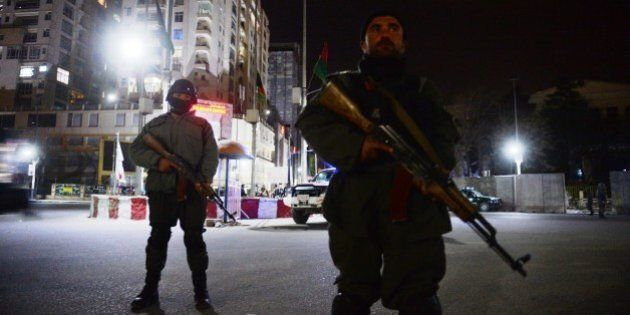 Afghan policemen block a road as they stands guard near the security perimeter setup around the Serena...