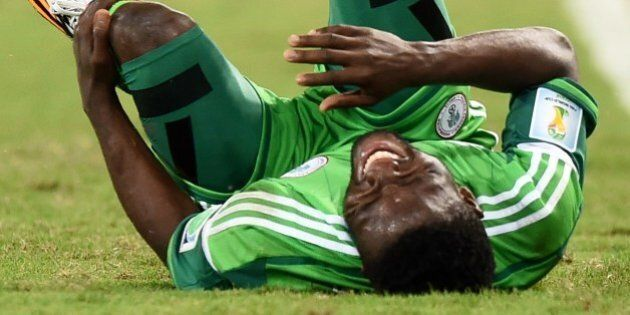 Nigeria's forward Michael Babatunde reacts in pain after falling during the Group F football match between...